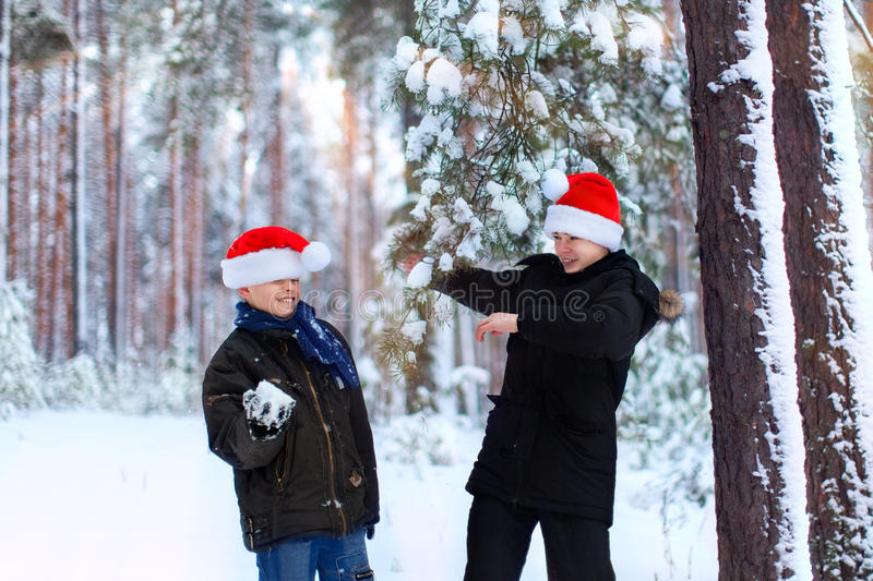 Two teenagers in Christmas hats Santa Claus having fun in the sn. Ow-covered forest playing in the snow stock image