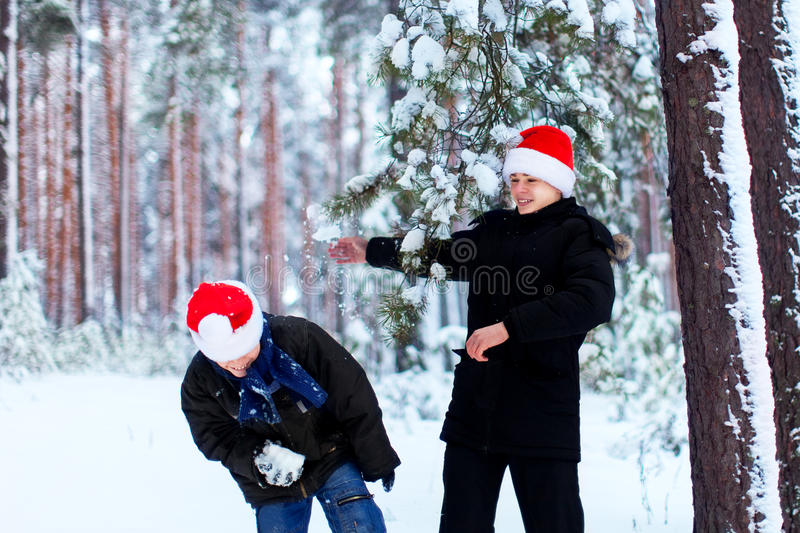 Two teenagers in Christmas hats Santa Claus having fun in the sn. Ow-covered forest playing in the snow royalty free stock photos