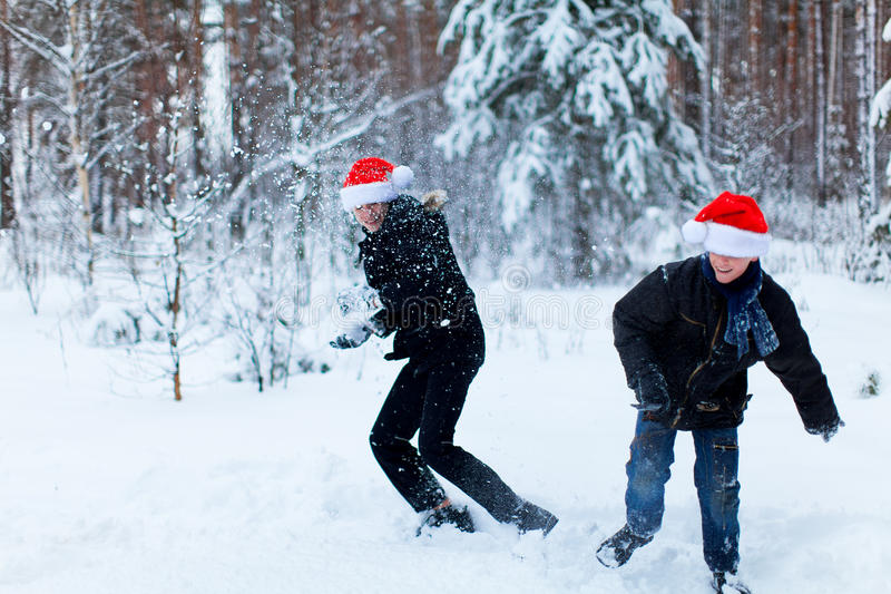 Two teenagers in Christmas hats Santa Claus having fun in the sn. Ow-covered forest playing in the snow royalty free stock images