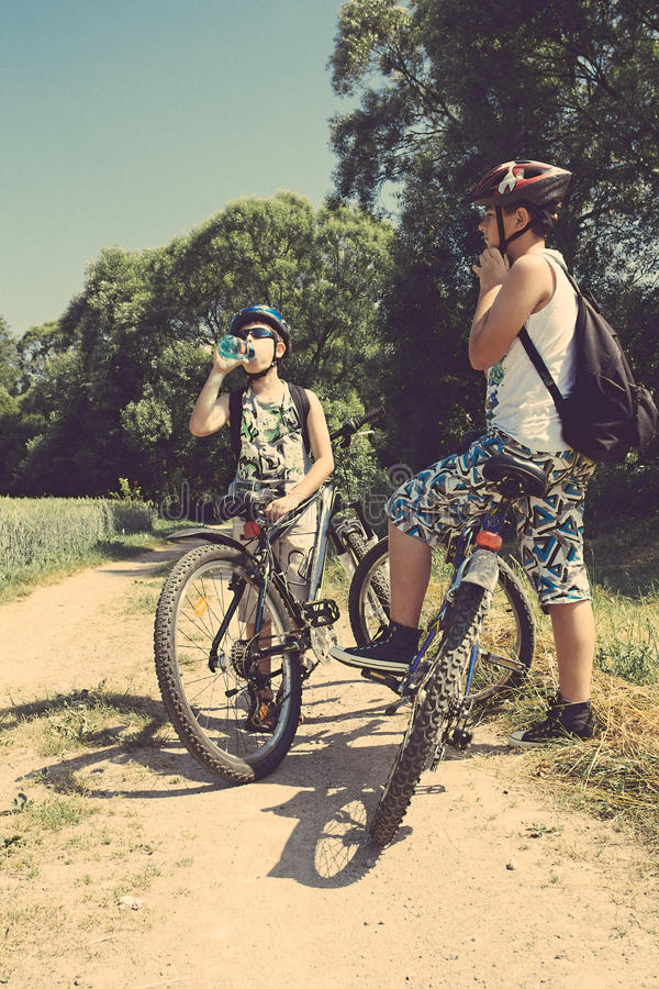 Two teenagers relaxing on a bike trip stock photo