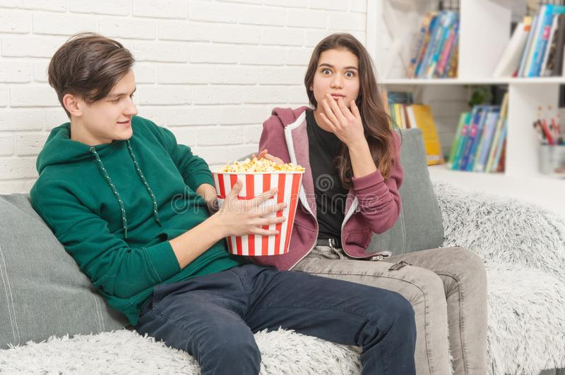 Two teenagers are sitting on the couch watching TV royalty free stock photography