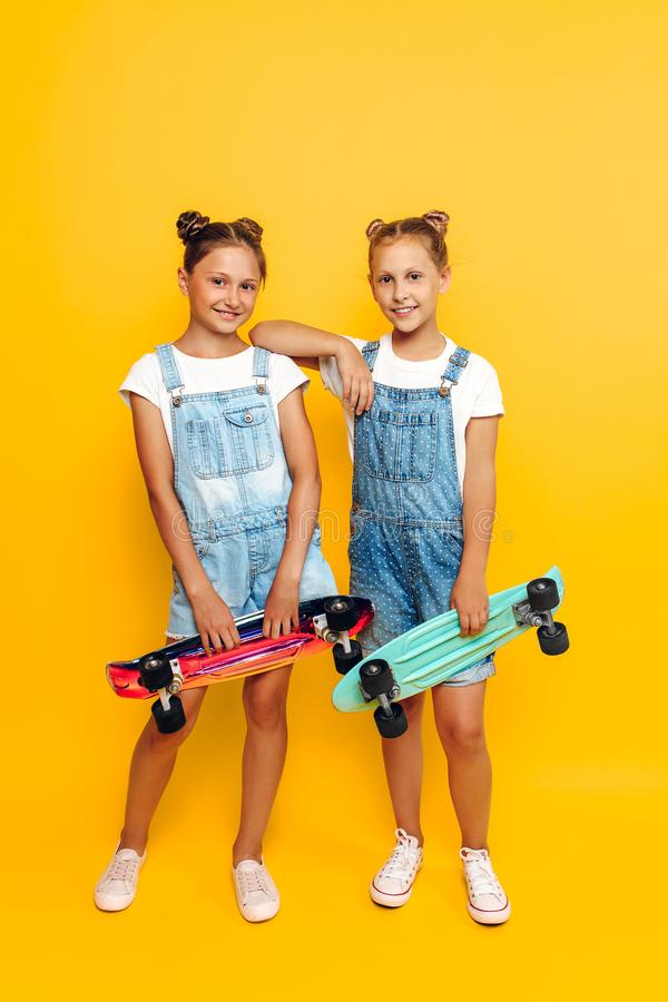 Two teenagers, stylish children posing with skateboards in their hands on a yellow background royalty free stock photo