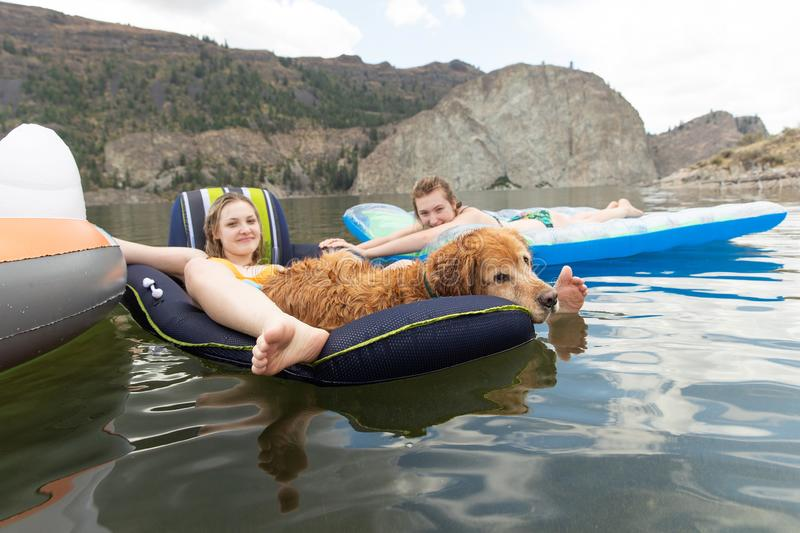 Two teenage girls and a golden retriever dog lounge comfortably on inflatables at a lake stock image