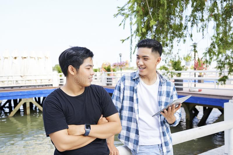 Two teens using tablet pc outdoors royalty free stock photos