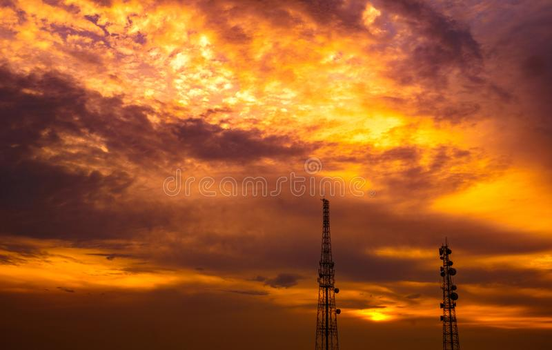 Two telecommunication towers on dramatic dark-orange sky. And cumulus clouds background stock photo