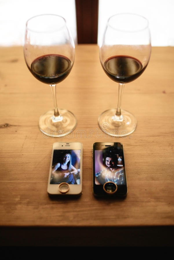 Two telephones, rings and two glasses of wine on a table stock image