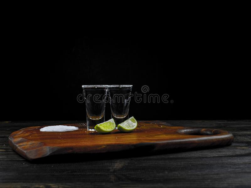 Two tequila silver shots with fresh lime and sea salt on wooden board and dark background stock images