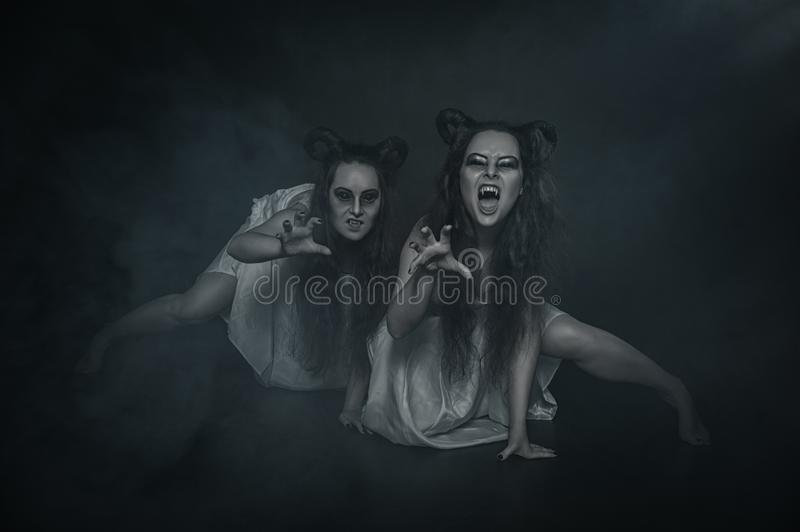 Two terrible ghost vampire on dark background. Two terrible ghost vampire with horns on dark background stock image
