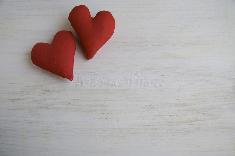 Two textile red hearts on a white wooden background stock photography
