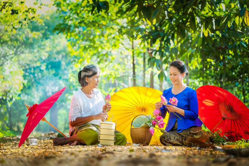 Two Thai women, two people folded pink lotus go to the temple. Two Thai women, two people folded pink lotus to go to the temple this morning royalty free stock photo