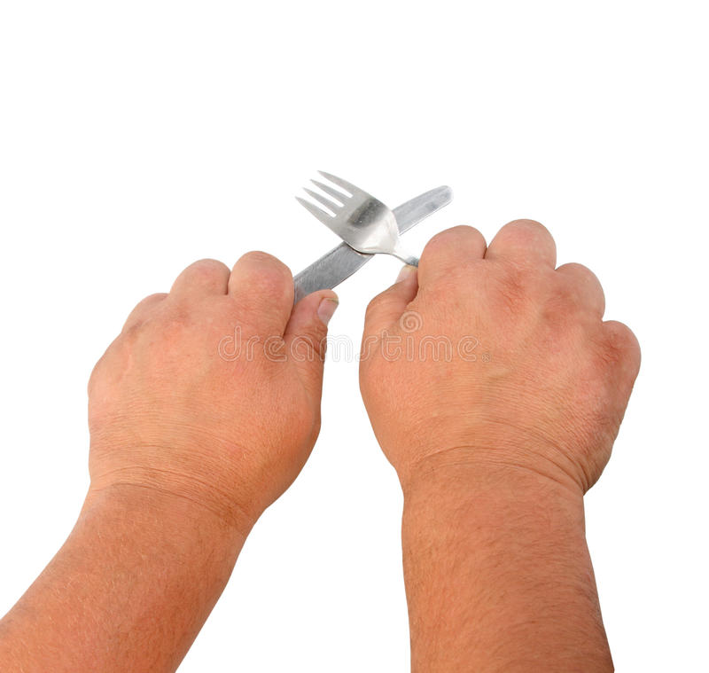 Two thick hands with knife and plug royalty free stock photo