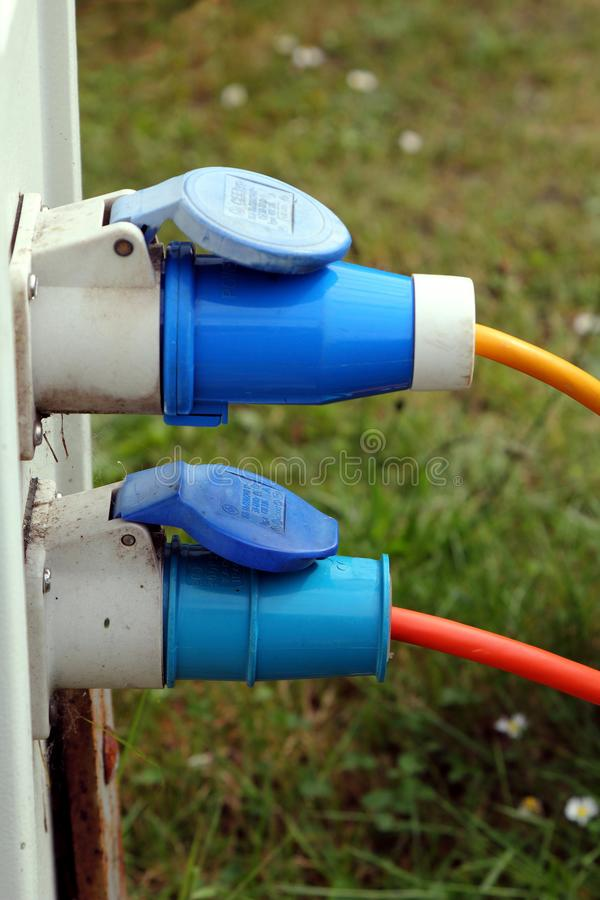 Two three pin outside power plugs connected to a campsite water and electricity supply point royalty free stock image