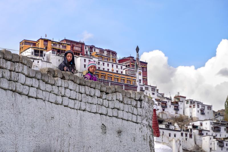 The two tibetan girls staying and looking from the wall royalty free stock image