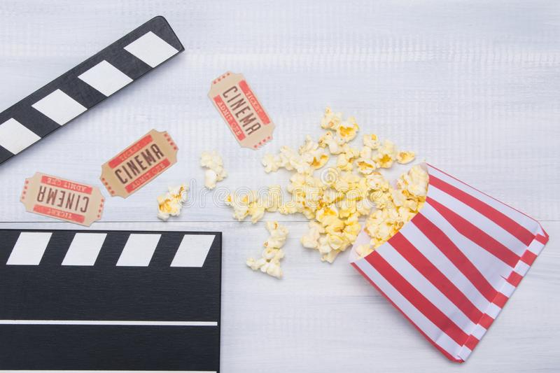 Two tickets to the cinema, on a wooden background in the arrangement of the movie clapper with a row strewn with popcorn royalty free stock images
