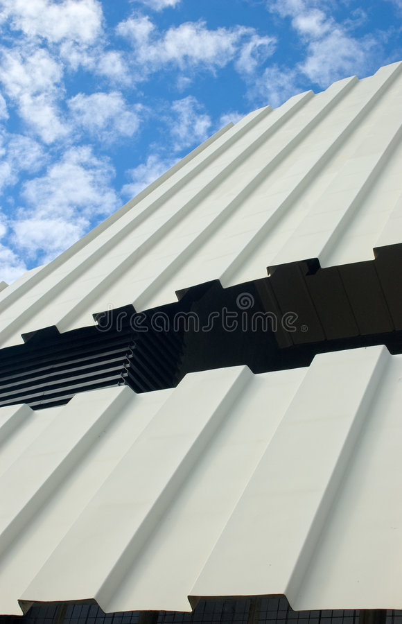 Two-tiered corrugated iron roof against cloudy sky royalty free stock image