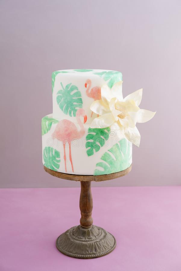 Tropical wedding cake. Two tiered tropical wedding cake with fondant, tropical wafer paper leaves and flamingos with a big golden statement flower on wooden cake stock images
