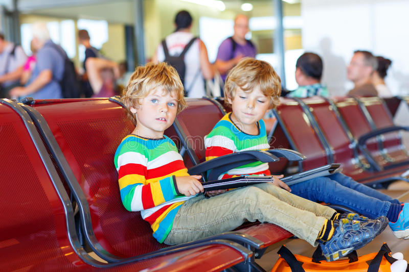 Two tired little sibling boys at the airport. Two tired little sibling kids boys at the airport, traveling together. Upset children waiting and playing with stock photography