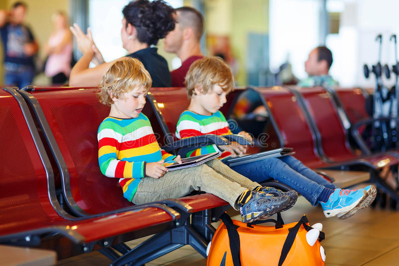 Two tired little sibling boys at the airport. Two tired little sibling kids boys at the airport, traveling together. Upset children waiting and playing with stock photo