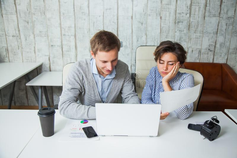 Two tired students cooperate work together office business teamwork. stock image