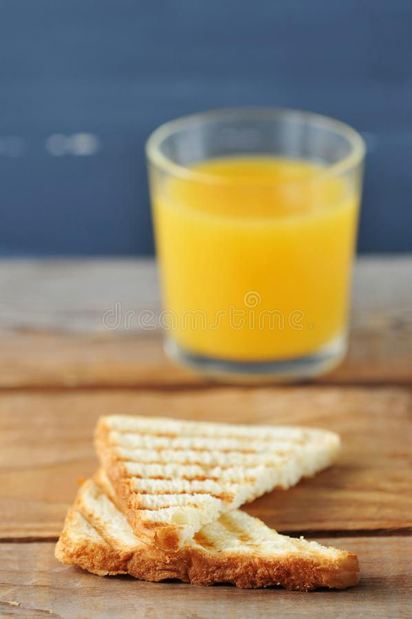 two toast bread closeup on a background of a glass of orange juice stock images