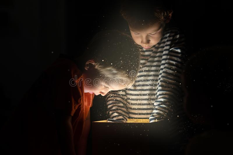 Two toddler boys standing over golden gift box with magical lights and glitters coming out stock image
