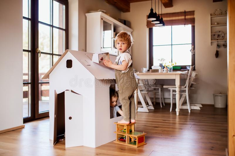 Two toddler children playing with a carton paper house indoors at home. royalty free stock photos