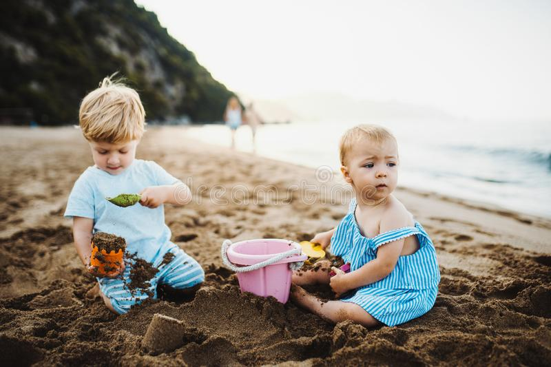 Two toddler children playing on sand beach on summer holiday. royalty free stock photo