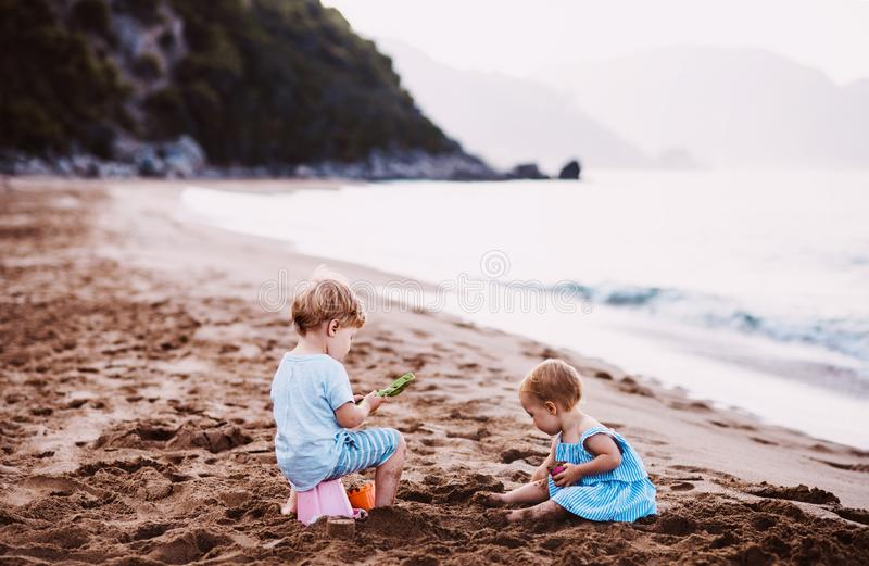 Two toddler children playing on sand beach on summer holiday. stock photography