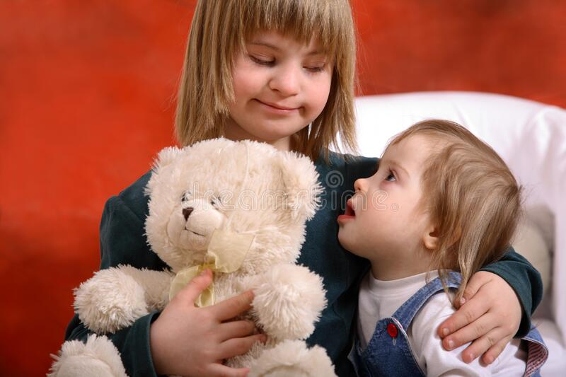 Two toddlers holding each other. Two kids holding each other. One of the children has down Syndrome royalty free stock photo