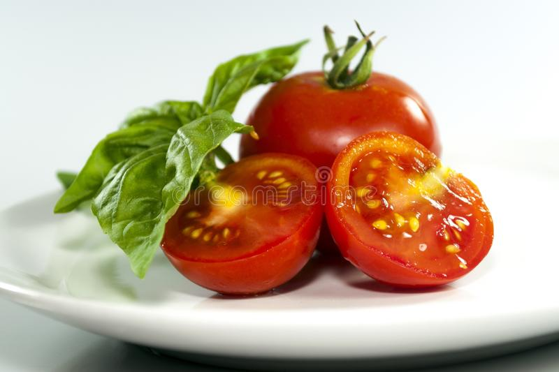 Two tomatoes in a white plate. Two tomatoes and a basil leaf on a white plate isolated on a white background royalty free stock image