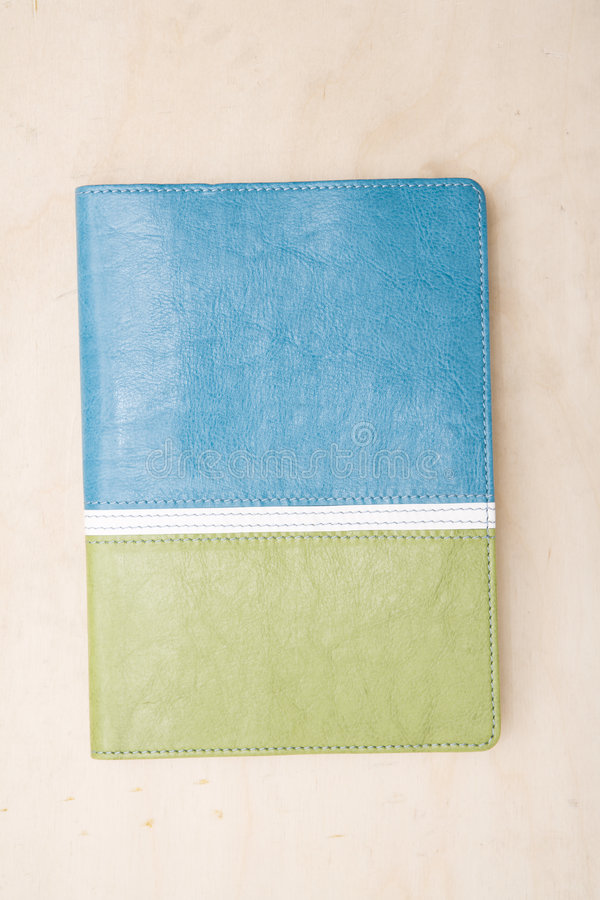 Two tone blue and green note book. Cover of a two tone blue and green note book photographed directly above sitting on a wood table royalty free stock photography