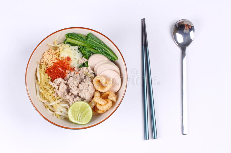 Two tone noodle ,white and yellow, with tom yum. Two tone noodle ,white and yellow, with tom yum topped minced pork ,chili ,minced nut ,boiled kale , sliced royalty free stock images