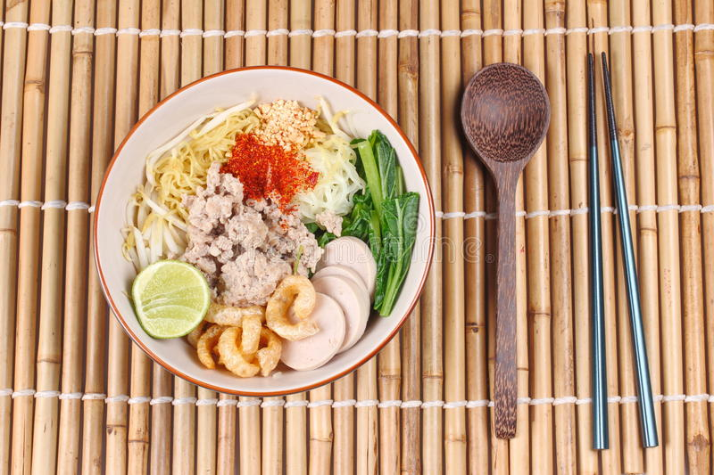 Two tone noodle ,white and yellow, with tom yum. Two tone noodle ,white and yellow, with tom yum topped minced pork ,chili ,minced nut ,boiled kale , sliced stock photo