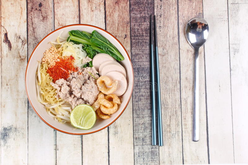 Two tone noodle ,white and yellow, with tom yum. Two tone noodle ,white and yellow, with tom yum topped minced pork ,chili ,minced nut ,boiled kale , sliced royalty free stock photography