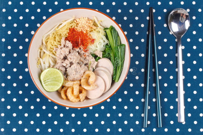 Two tone noodle ,white and yellow, with tom yum. Two tone noodle ,white and yellow, with tom yum topped minced pork ,chili ,minced nut ,boiled kale , sliced stock photography