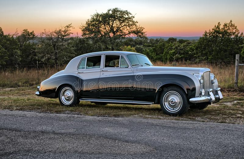 Sunset behind vintage luxery limousine on a Texas country road. stock photography