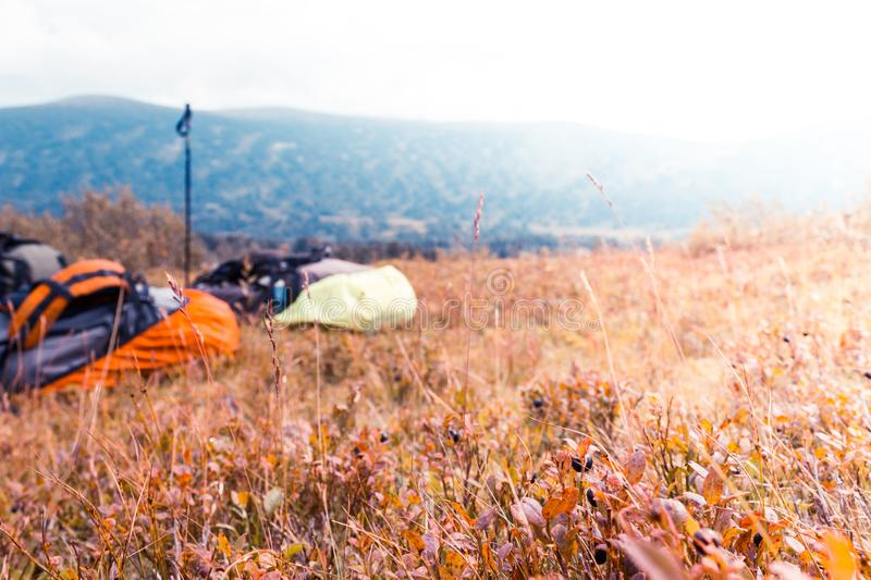 Two tourist backpack on autumn meadow in a mountain valley. royalty free stock image