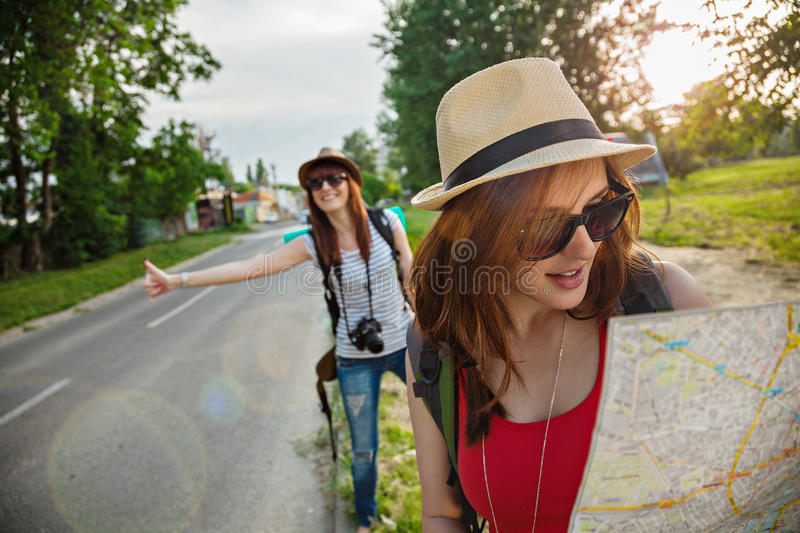 Two Tourist Girl Hitchhiking. Two Young Tourist Girl Hitchhiking On The Road royalty free stock photo