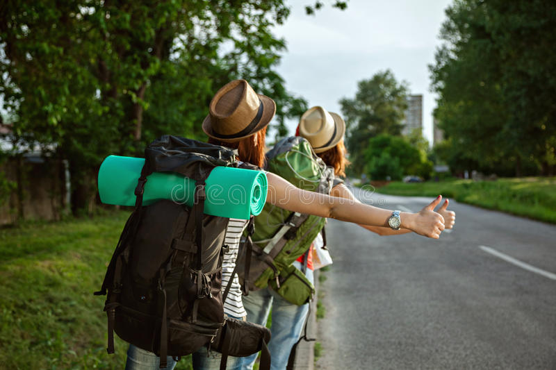 Two Tourist Girls Hitchhiking. Two Young Tourist Girls Hitchhiking On The Road stock image