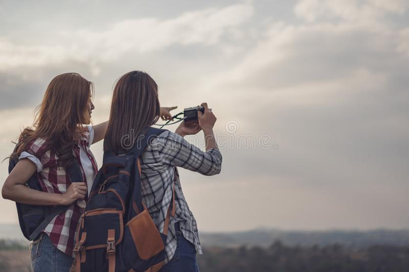 Two tourist woman taking a photo with camera in nature. Two tourist women taking a photo with her camera in nature royalty free stock photography
