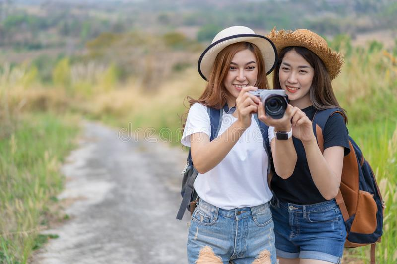 Two tourist woman taking a photo with camera in nature. Two tourist women taking a photo with her camera in nature stock image