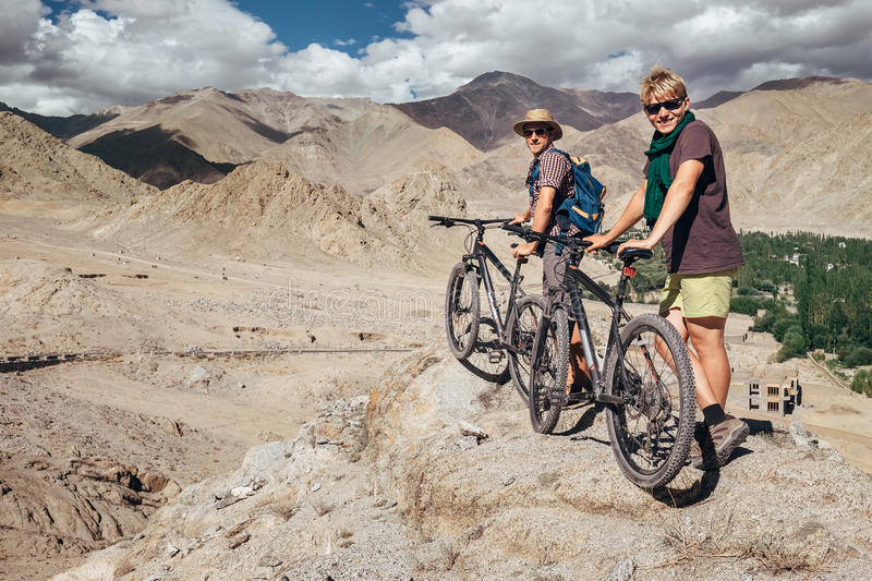 Two tourists with bikes explore Himalaya mountain region stock photography