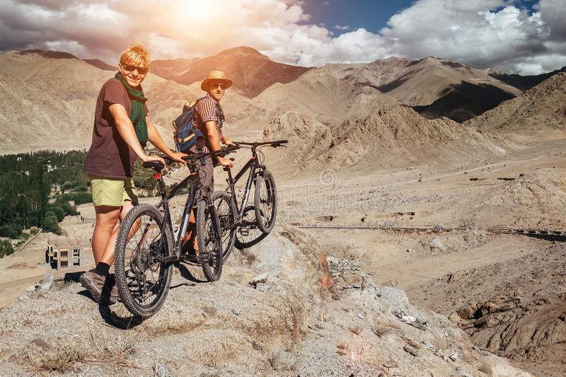 Two tourists with bikes explore Himalaya mountain region royalty free stock image