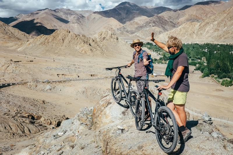 Two tourists with bikes explore Himalaya mountain region stock image