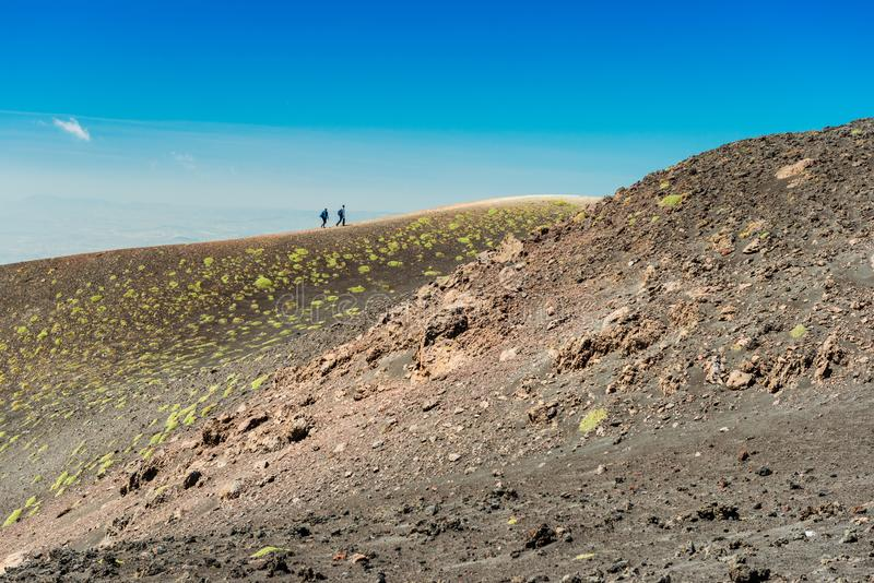 Two tourists do a hiking tour around the edge of a volcanic crater, Mount Etna, Sicily, Italy stock images
