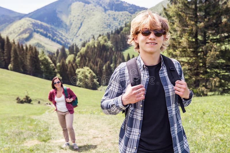 Two tourists going up on the mountain hill stock photos