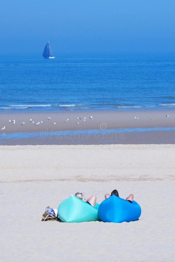 Two tourists are lying on inflatable deck chairs on hammocks. Wide sandy beach near the North Sea. Beautiful promenade of Ostend, royalty free stock image
