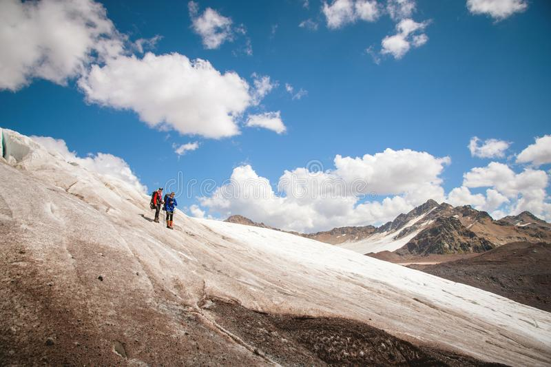 Two tourists, a man and a woman with backpacks and cats on their feet, stand on the ice in the background of the. Two tourists, a men and a women with backpacks stock photos