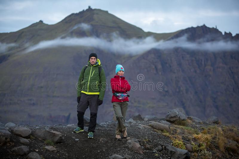 Two tourists, a man and a woman are standing on a hill against the background of volcanic mountains royalty free stock photography