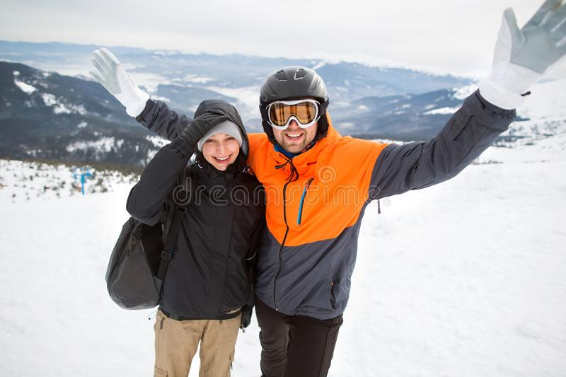 Two tourists skier on top of the mountain wearing a helmet, hap royalty free stock photo